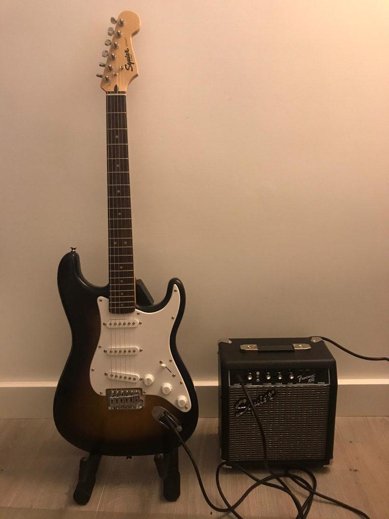 Um guitarra (cor sunburst) e um amplificador, lado a lado.